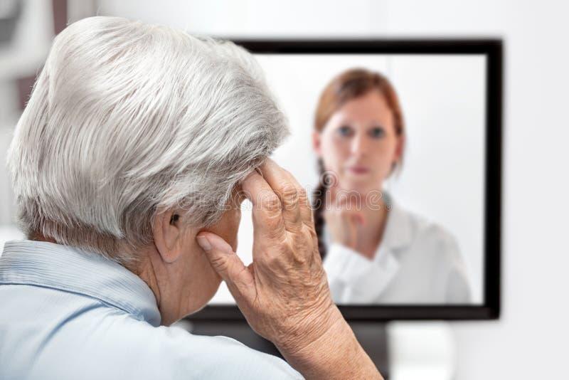 Donna anziana con l'emicrania, medico sul monitor che ascolta, co fotografie stock