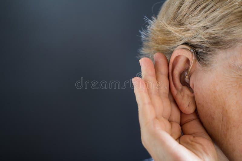 Donna anziana con la protesi acustica su fondo grigio Sordità concentrata fotografia stock