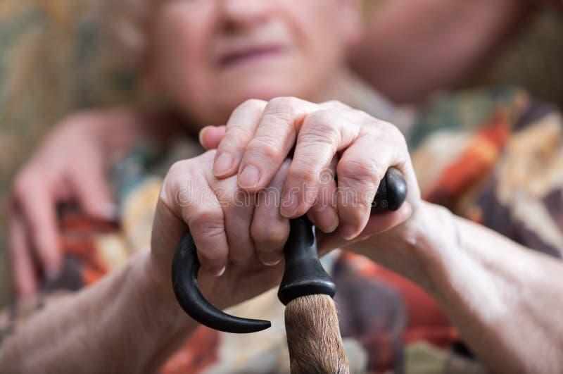 Donna anziana con le sue mani su una canna fotografie stock libere da diritti