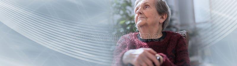 Donna anziana con le sue mani su una canna; insegna panoramica fotografia stock