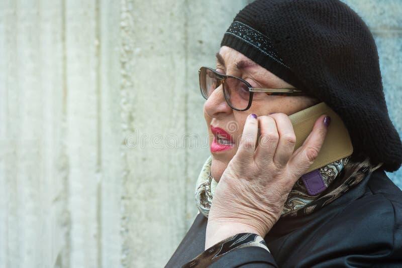 Donna anziana con trucco luminoso che parla sul telefono all'aperto fotografia stock libera da diritti
