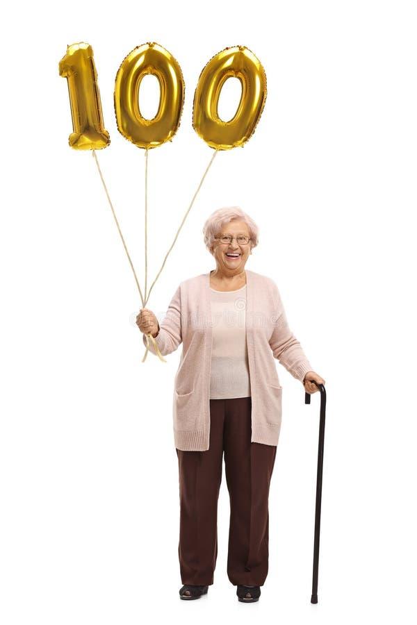 Donna anziana con un pallone dorato di numero cento e una canna fotografia stock libera da diritti