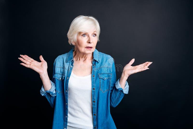 Donna anziana confusa che sta sul fondo nero fotografia stock