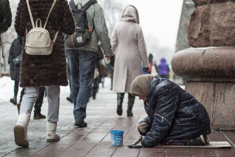 Donna anziana del mendicante sulle sue ginocchia che elemosina l'alimento dai passanti su una via della città fotografia stock