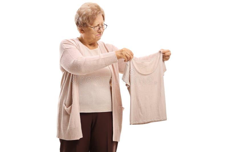 Donna anziana deludente che esamina una blusa restretta immagine stock