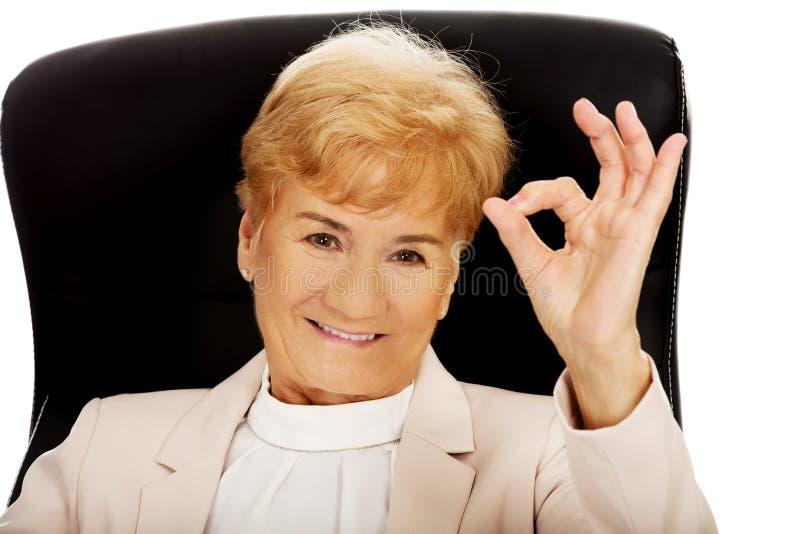 Donna anziana di affari di sorriso che si siede sulla poltrona e sul segno giusto di manifestazione fotografie stock