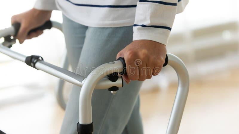 Donna anziana disabile in piedi sola a camminare con un telaio, chiusa fotografie stock libere da diritti