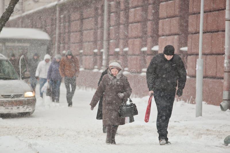 Donna anziana e giovane che camminano attraverso la neve di azionamento Blizza fotografia stock libera da diritti