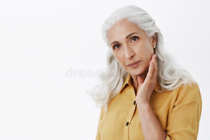 Donna anziana elegante sicura e femminile con capelli bianchi lunghi in trench giallo alla moda che tocca delicatamente fronte e immagine stock libera da diritti