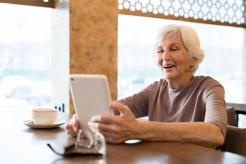 Donna anziana emozionante allegra che gode della lettura in caffè fotografie stock