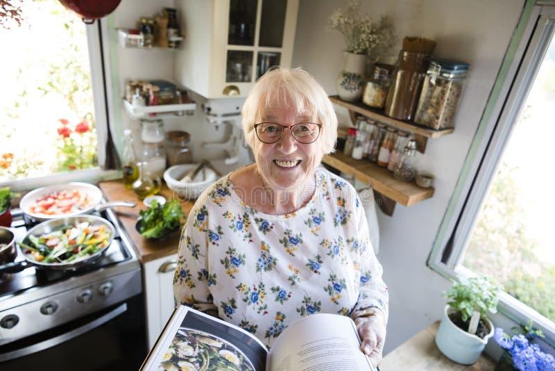 Donna anziana felice che legge un libro di cucina fotografia stock libera da diritti