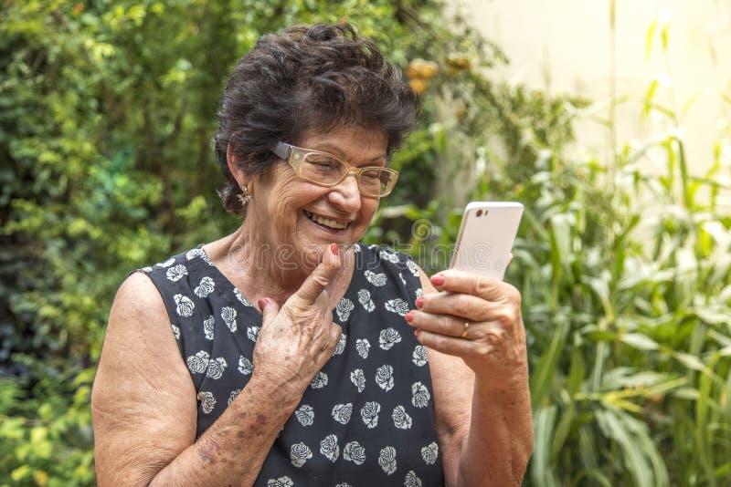 Donna anziana felice che per mezzo del cellulare fotografia stock libera da diritti