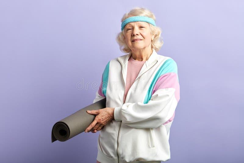 Donna anziana felice che tiene una stuoia di yoga immagini stock libere da diritti