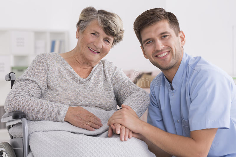 Donna anziana felice con l'infermiere maschio immagine stock