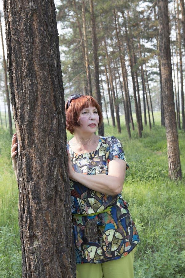 Donna anziana felice in un parco di estate immagini stock libere da diritti