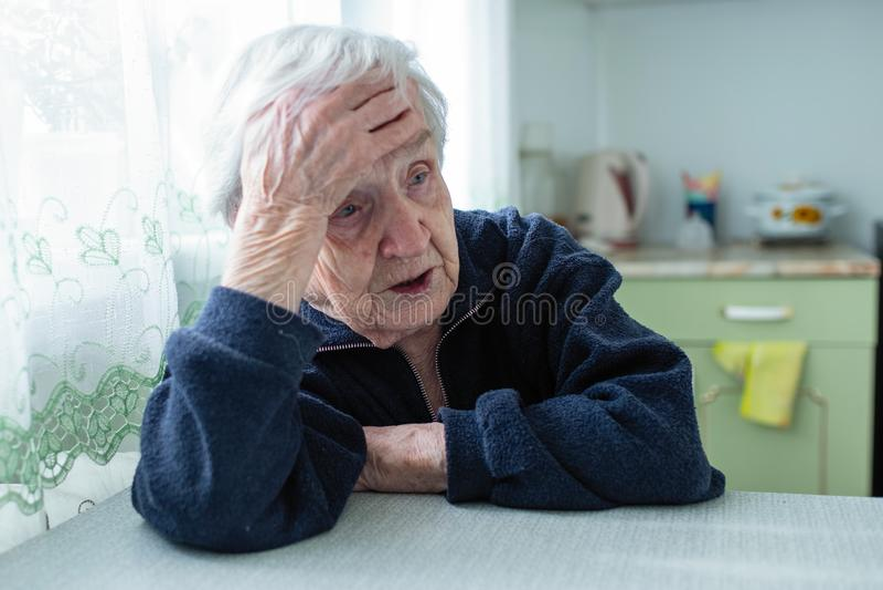 Donna anziana frustrata che si siede a casa alla tavola fotografie stock libere da diritti