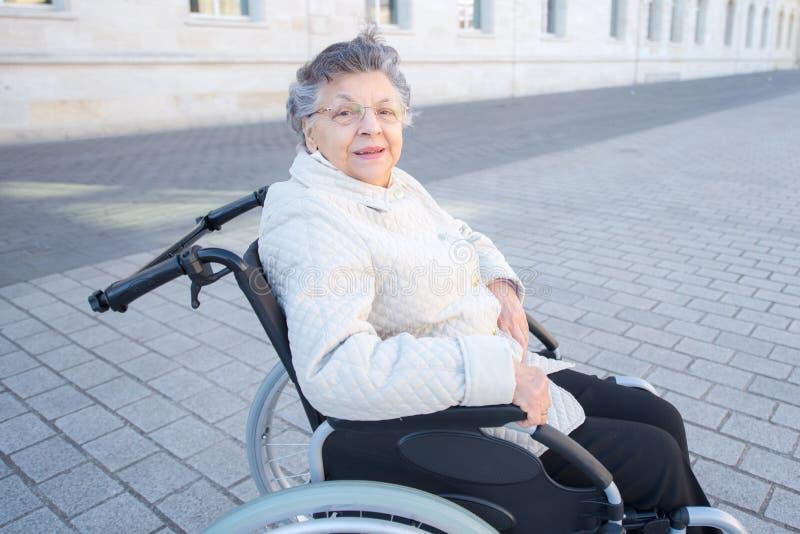 Donna anziana handicappata che si siede in sedia a rotelle all'aperto fotografia stock