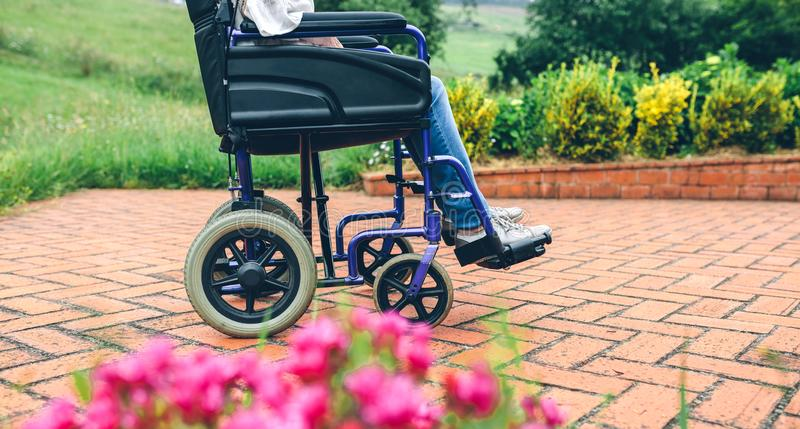 Donna anziana irriconoscibile in una sedia a rotelle fotografie stock