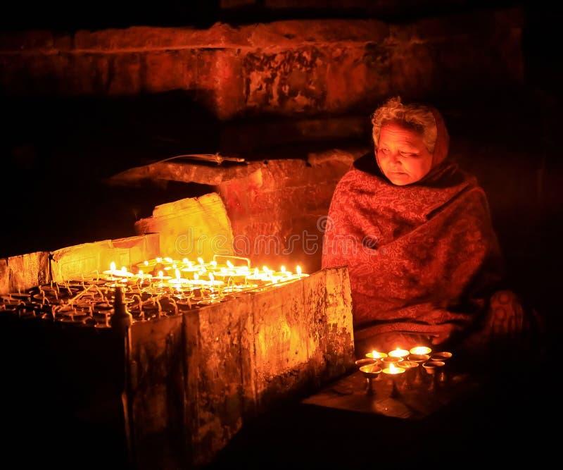 Donna anziana nepalese che prega con le candele Kathmandu, Nepal sopra immagini stock