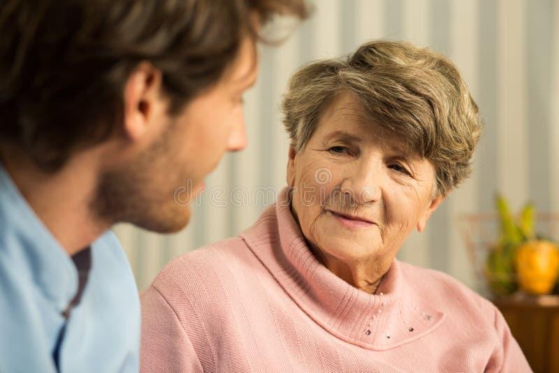 Donna anziana positiva con il personale sanitario immagini stock libere da diritti