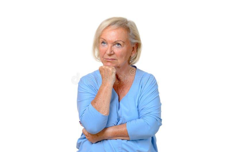Donna anziana premurosa che fissa su nell'aria fotografia stock