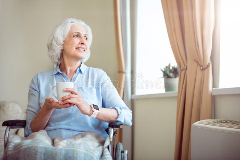 Donna anziana in sedia a rotelle che tiene tazza immagini stock