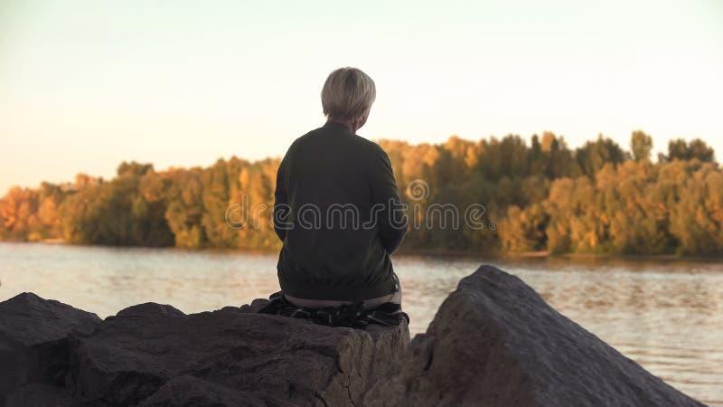 Donna anziana sola che si siede vicino al lago ed alla solitudine di lancio delle pietre, vista della parte posteriore fotografia stock
