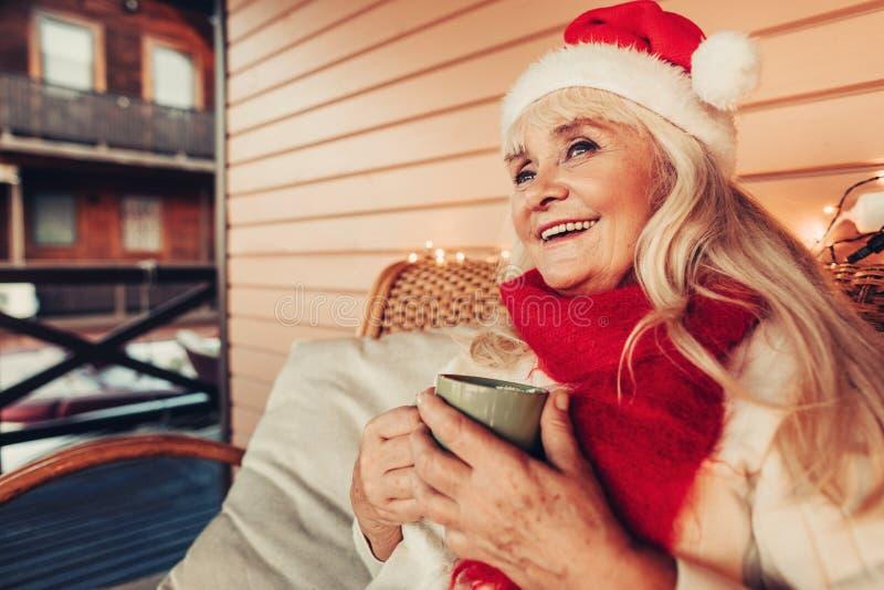 Donna anziana sorridente gioiosa che individua sul portico decorato fotografie stock libere da diritti