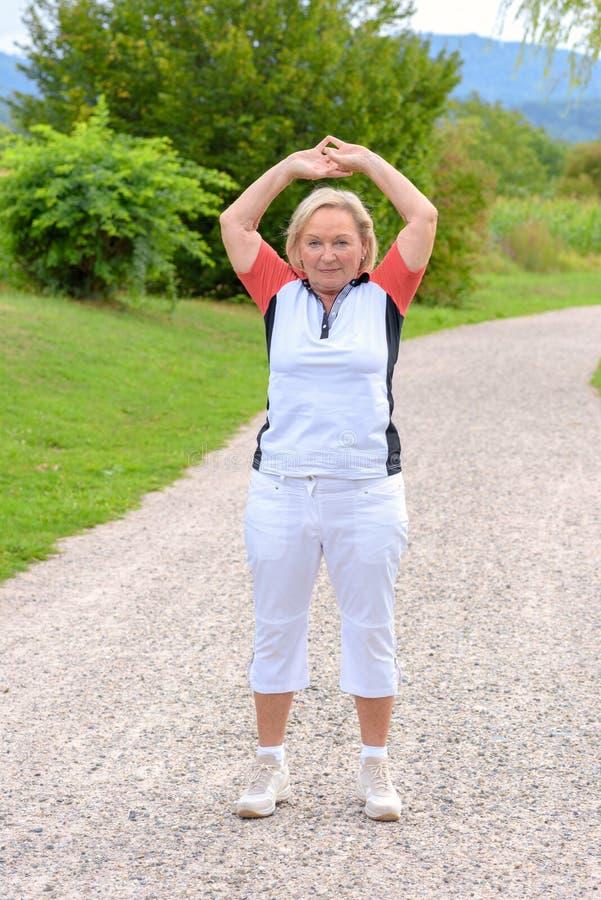 Donna anziana sportiva che fa gli esercizi di sport fotografia stock