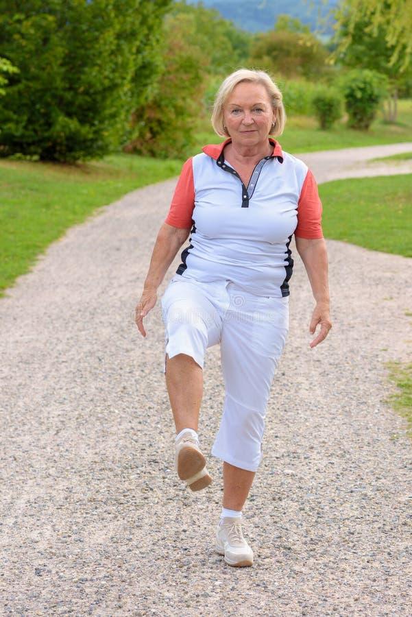 Donna anziana sportiva che fa gli esercizi di sport immagine stock