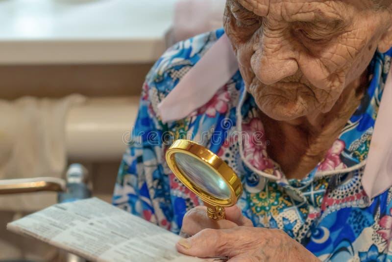 Donna anziana stessa con la lente che prova a leggere da un giornale la nonna 90 anni legge alla tavola con la lente fotografia stock