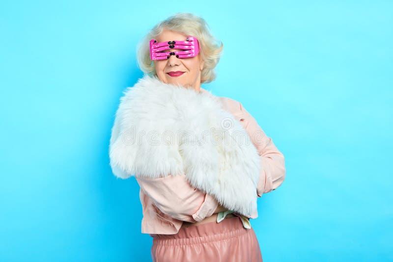 Donna anziana in vetri rosa alla moda fynny che esaminano la macchina fotografica immagini stock