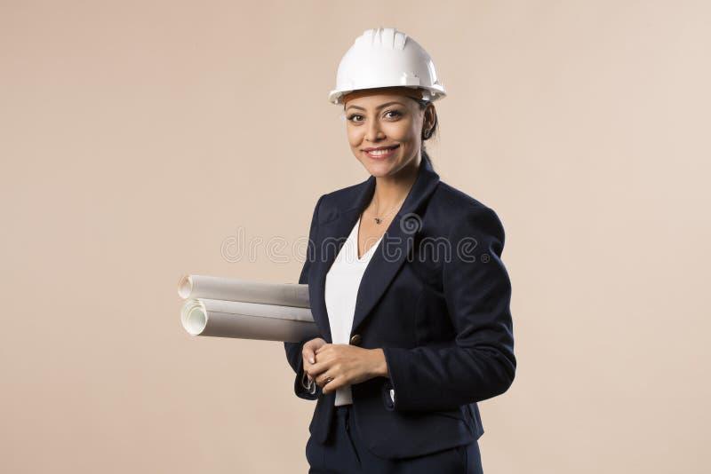 Donna araba abbastanza giovane dell'ingegnere dell'architetto isolata con il casco immagini stock libere da diritti