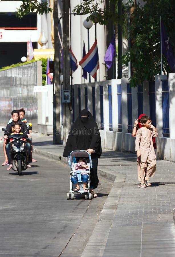 Donna araba che spinge un passeggiatore di bambino fotografia stock