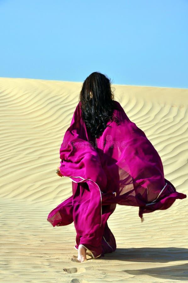 Donna araba del brunette che cammina attraverso il deserto fotografie stock libere da diritti