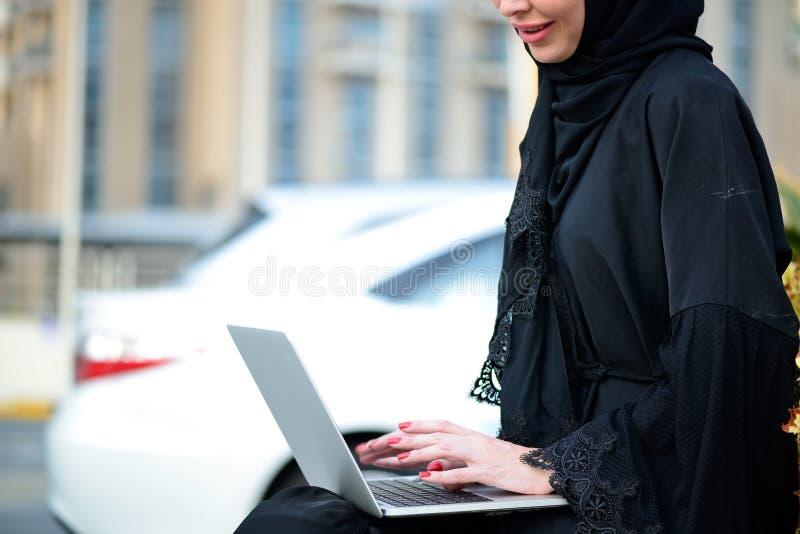 Donna araba di affari di Emarati che per mezzo del computer portatile immagini stock