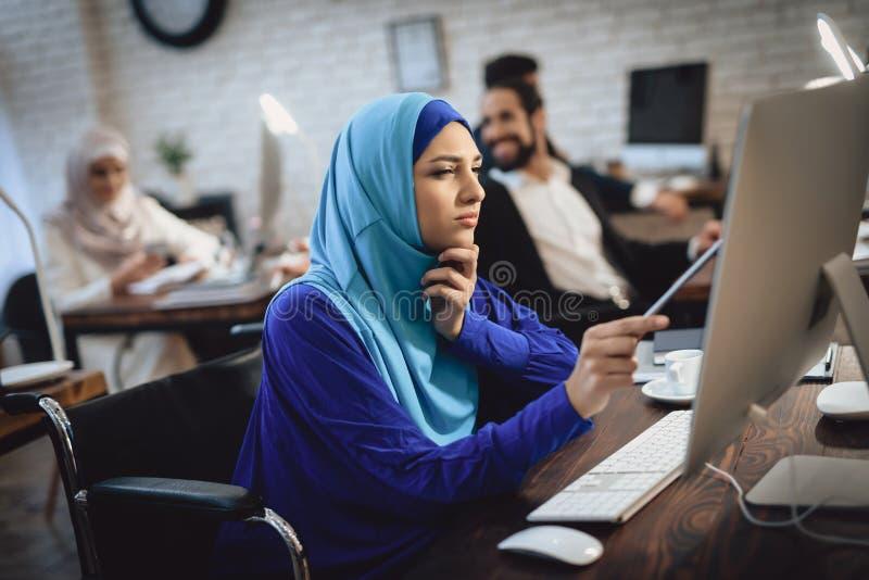 Donna araba disabile in sedia a rotelle che funziona nell'ufficio La donna sta lavorando al desktop computer fotografia stock libera da diritti