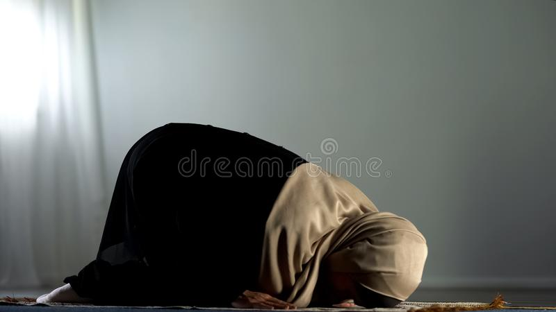 Donna araba inginocchiata che prosterna sulla coperta pregante islamica, culto religioso, fede fotografia stock libera da diritti