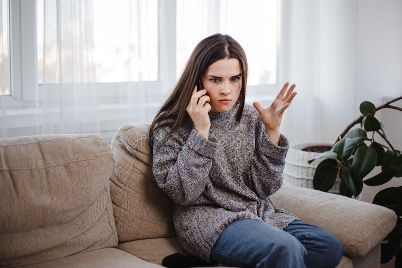 Donna arrabbiata che discute durante la telefonata immagine stock