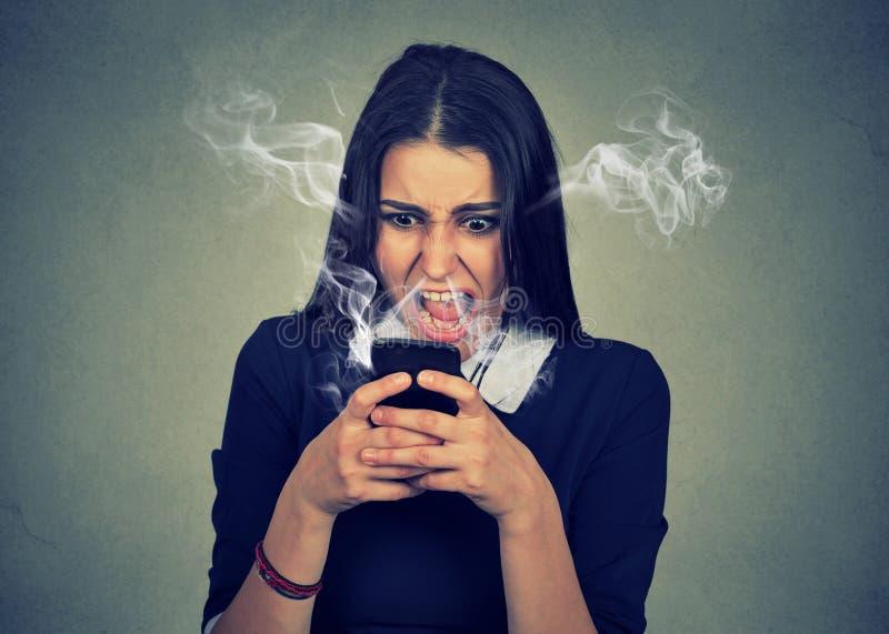 Donna arrabbiata che grida al suo telefono cellulare, infuriato con cattivo servizio fotografia stock libera da diritti