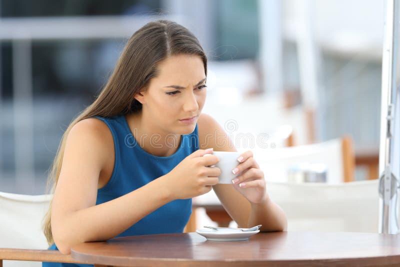 Donna arrabbiata che pensa in un terrazzo della caffetteria immagine stock
