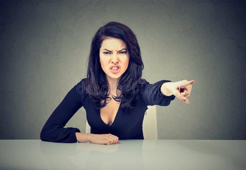 Donna arrabbiata di affari che si siede al a suoi scrittorio ed indicare di grido con il dito da uscire fotografie stock