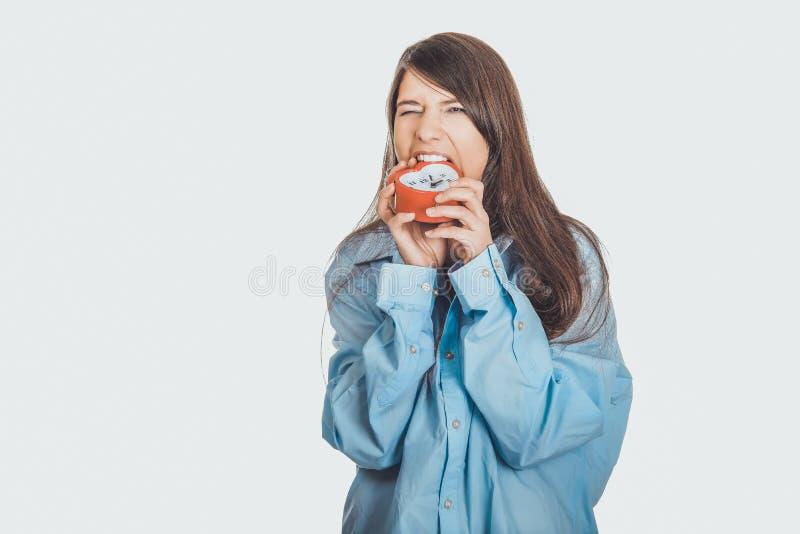 Donna arrabbiata in grande sveglia della tenuta della camicia fotografie stock