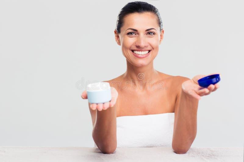 Donna in asciugamano che si siede alla tavola e che tiene barattolo crema immagini stock libere da diritti