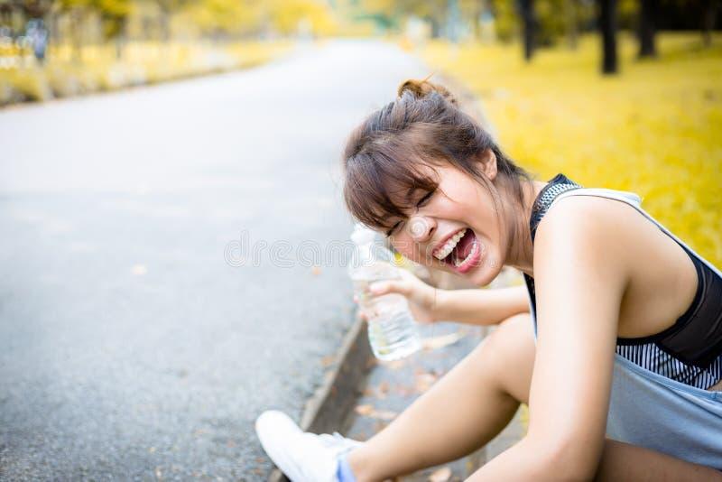 Donna asiatica affascinante del ritratto bella La ragazza attraente sta ridendosi perché la ragazza graziosa spruzza l'acqua tutt fotografia stock