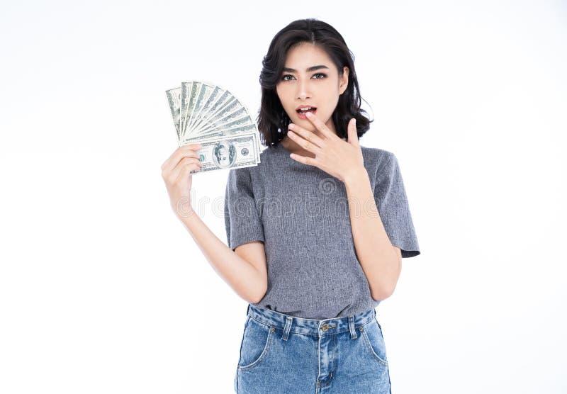 Donna asiatica allegra positiva sorpresa che tiene le banconote dei soldi e che esamina la macchina fotografica isolata contro fo fotografia stock