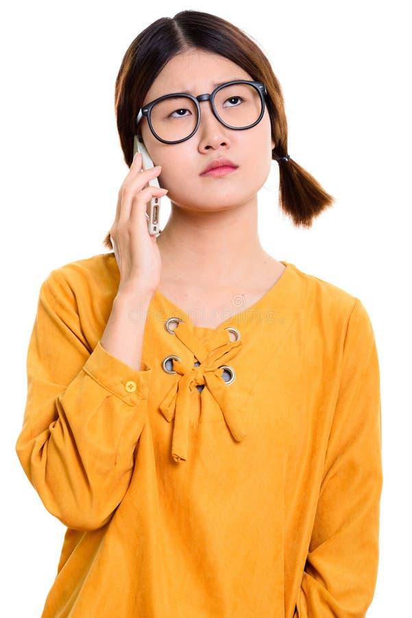 Donna asiatica annoiata dei giovani che parla sul telefono cellulare fotografie stock