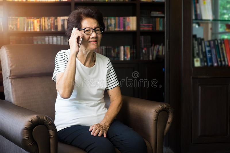 Donna asiatica anziana che per mezzo dello smartphone per parlare immagine stock