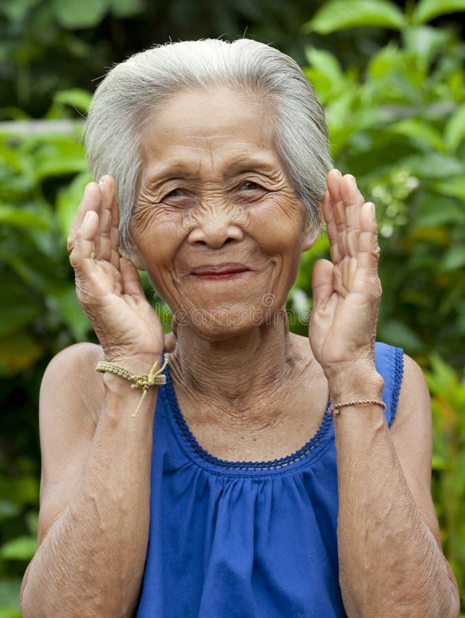 Donna asiatica anziana del ritratto con i gesti fotografie stock