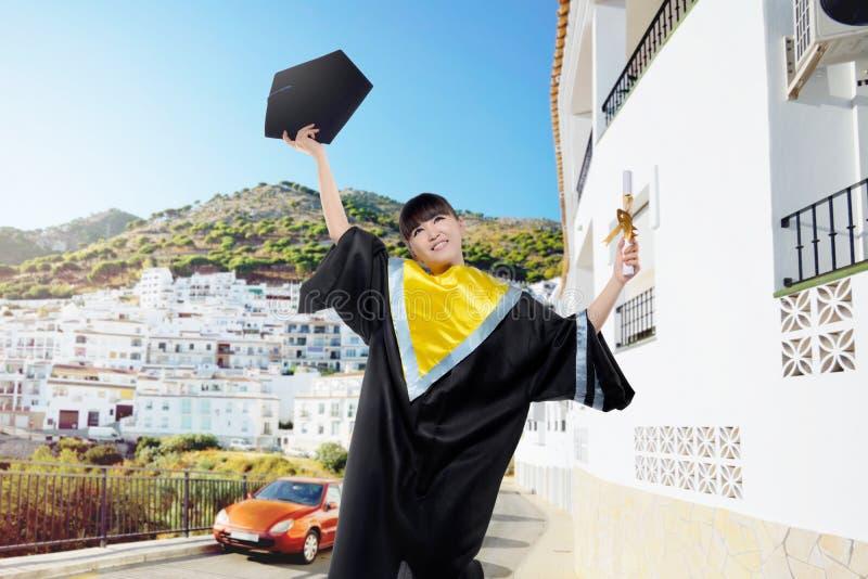 Donna asiatica attraente che getta il suo cappuccio di graduazione fotografia stock